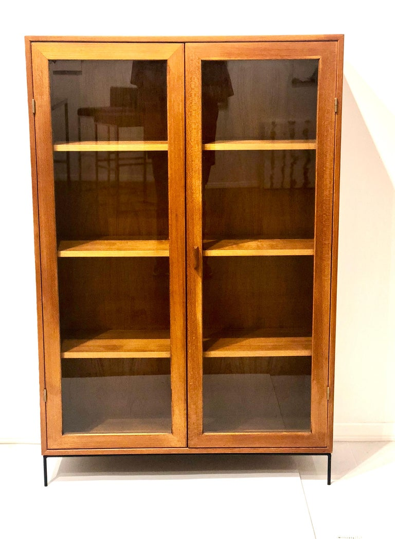 Beautiful and versatile Danish modern teak bookcase with a bevelled wood edge front shelves with double glass doors, and removable shelves, sitting solid iron base. Great size and very rare to find. The case has been completely refinished and is in