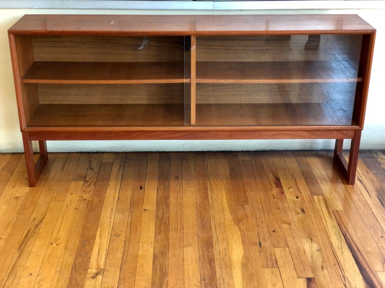 Versatile low cabinet bookcase in teak with glass sliding doors designed by Gunni Omann, for ACO Mobler Denmark, circa 1960's nice condition we have lightly sanded and oiled the piece looks great. With removable shelves.