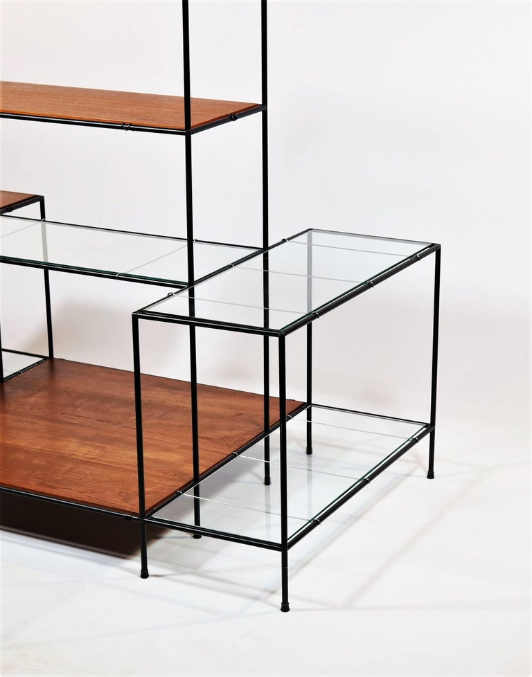 Ingenious Minimalist shelving or display unit designed by Poul Cadovius, Denmark, in the 1960s. The system consists of black metal tubes with patented connectors, floating teak wood and thick glass shelves. The minimalistic and modern looking