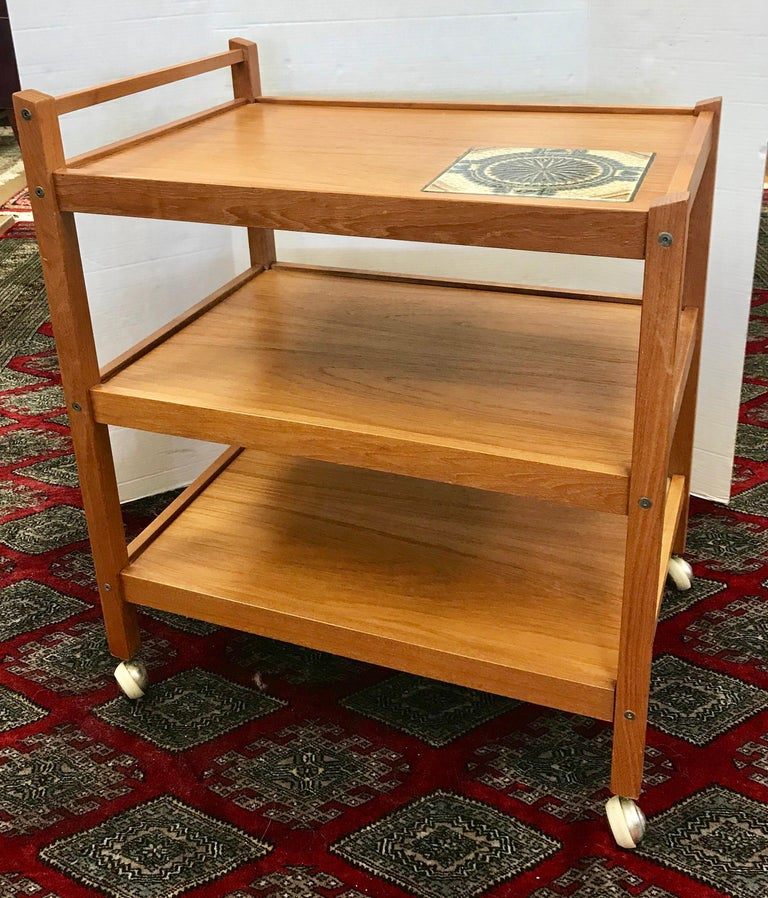 Danish vintage midcentury teak bar cart tea caddy trolley. This vintage original trolley hails from Denmark and is truly representative of the simplicity that is Danish design including the coveted tile insert at top. This trolley is all original,