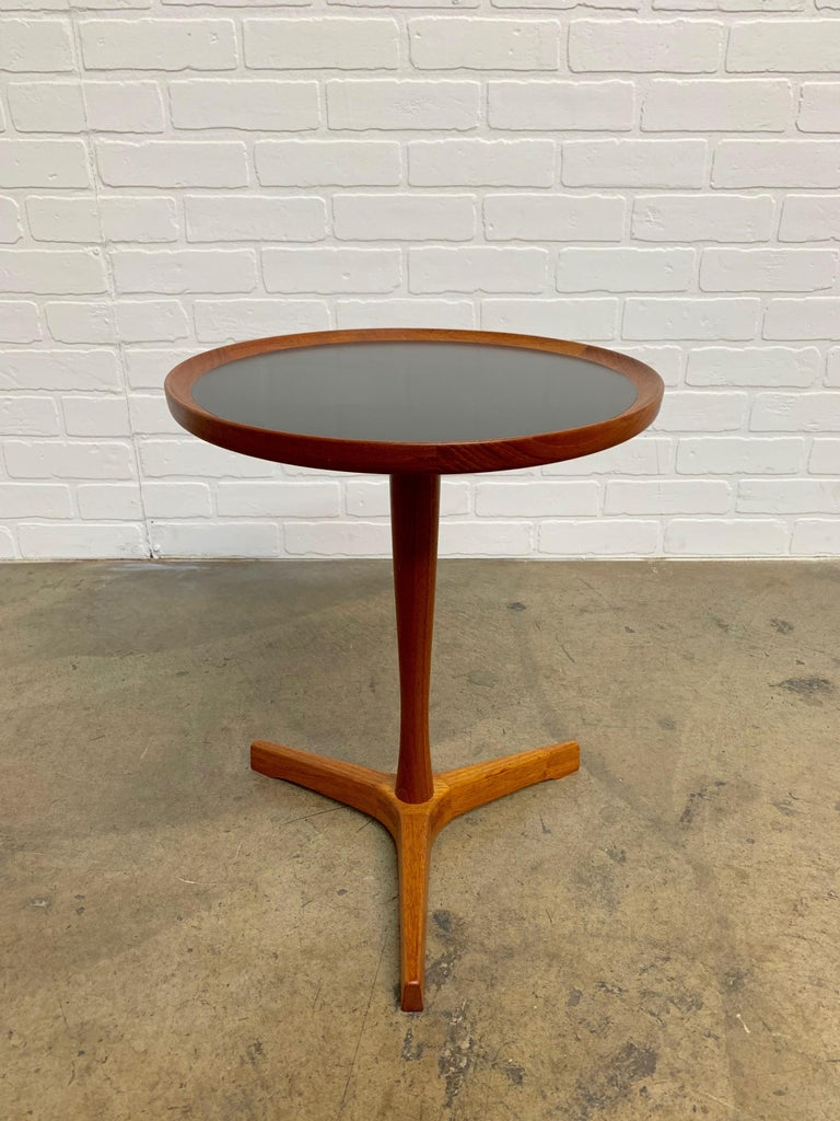 Designed by Hans C. Andersen, Denmark. This drink table has a black laminate inlaid top and a solid teak pedestal base.