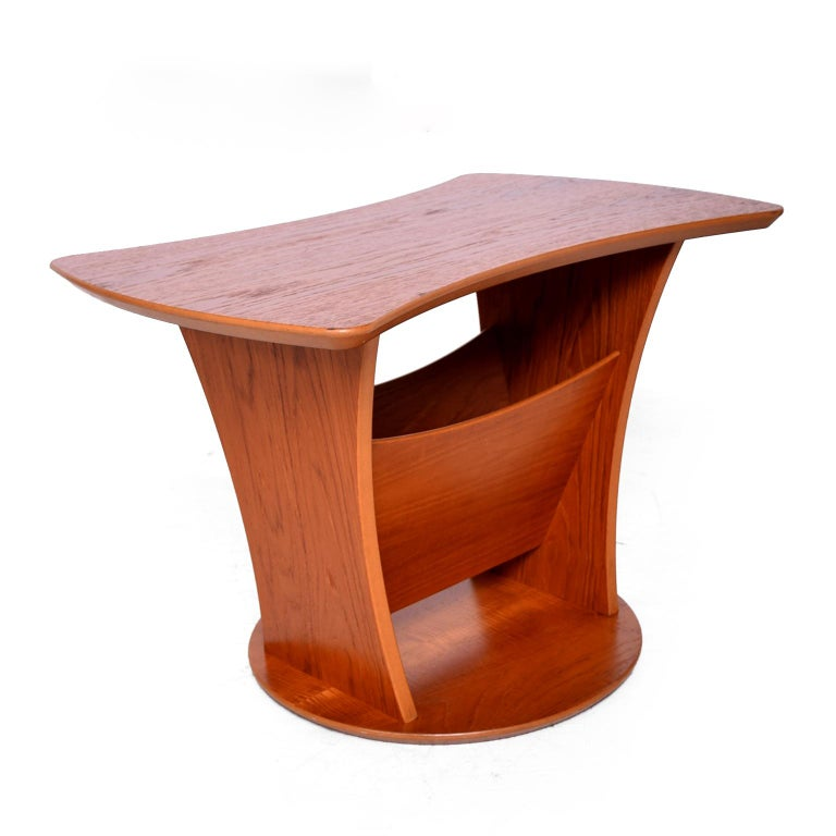 Sophisticated and Simple Sculptural side Table made of Teak Wood (veneer)  Denmark Circa 1980s.  Unusual sculptural design with round base and kidney shape top. There is a storage section underneath the top for magazines.  Unmarked, no apparent