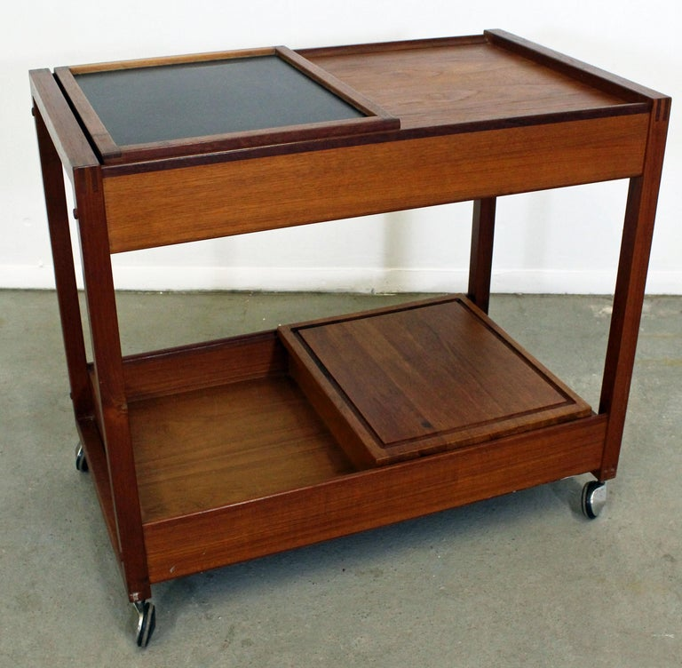 What a find. Offered is a very cool Danish modern teak bar cart. Features two sliding doors on top and bottom with compartments. It is also on wheels. Great for storage, serving drinks or food. It is in excellent condition, showing some age wear. It