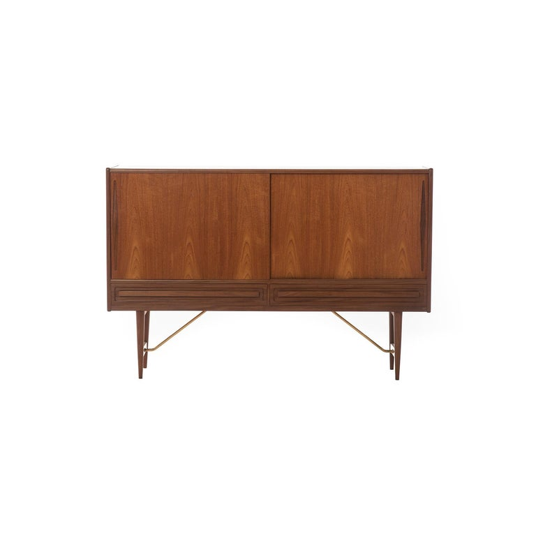 This Danish modern classic old growth teak credenza features sliding doors with inset finger pulls, 5 pull out silver drawers (two of which are felt lined), two adjustable shelves on the right, two half and one full shelf on the left (set), and two