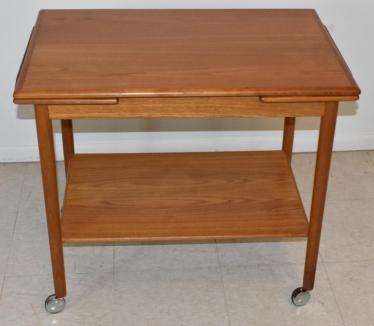 Danish modern teak bar / tea cart by Dyrlund. Two leaf pullouts and rolling chrome wheels.