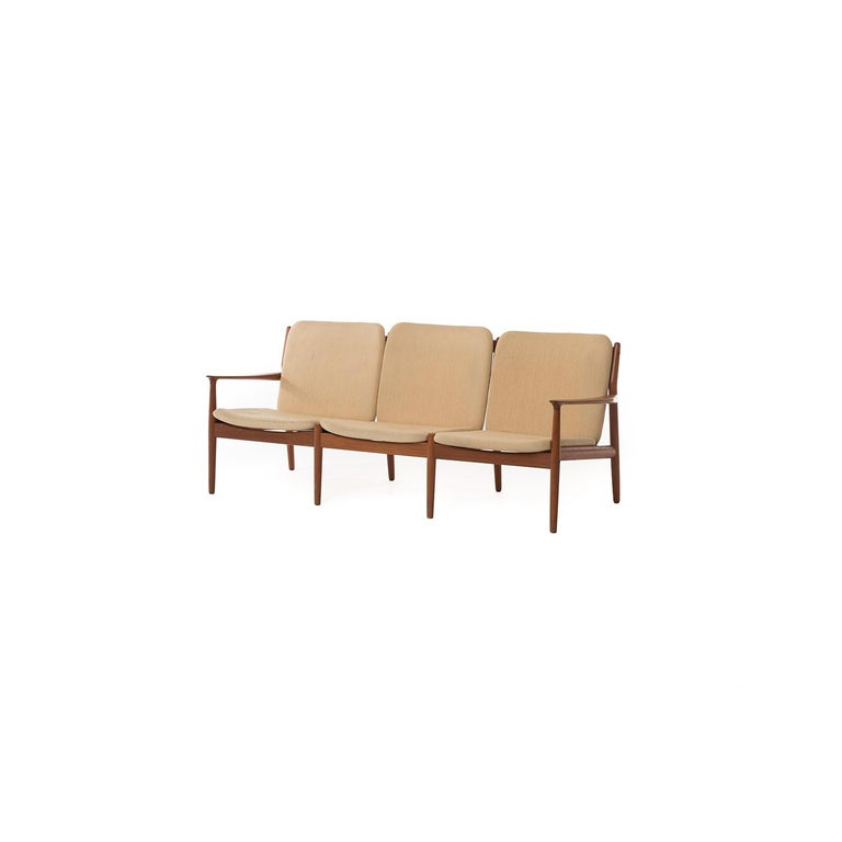 This elegant three-seat sofa rests atop a teak frame featuring sculptural arms. The slatted back makes it attractive from all angles.