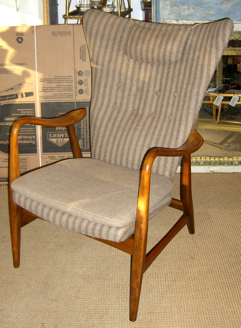 A stunning example of Danish modern design. Produced by Bovenkamp this wing back chair has unique free floating curved arms. The upholstery is original.