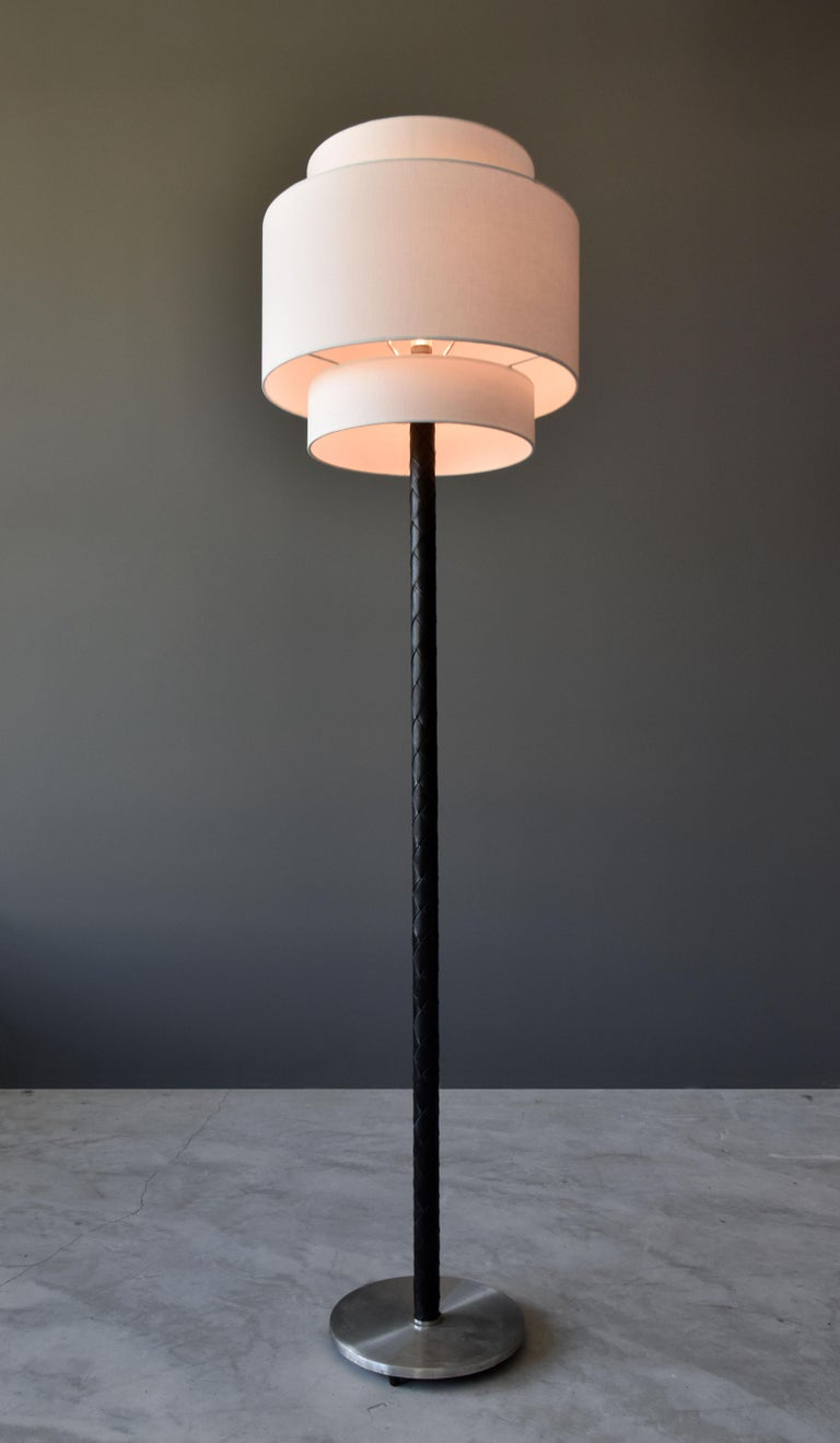 A Danish modernist floor lamp. Base of stainless steel, rod covered in braided black dyed leather. Handmade two-tier drum screen.