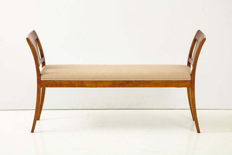 A Danish neoclassical birchwood window seat with geo-metric inlays, 19th century, with an upholstered seat between out curved armrests raised on sabre legs.