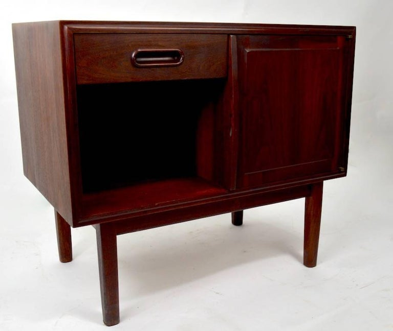Very good quality Danish modern night table, featuring one drawer, over an open storage cubby, flanked by a door which opens to reveal more storage, as shown. Solid walnut, in dark finish. This case has been professionally refinish, and is in
