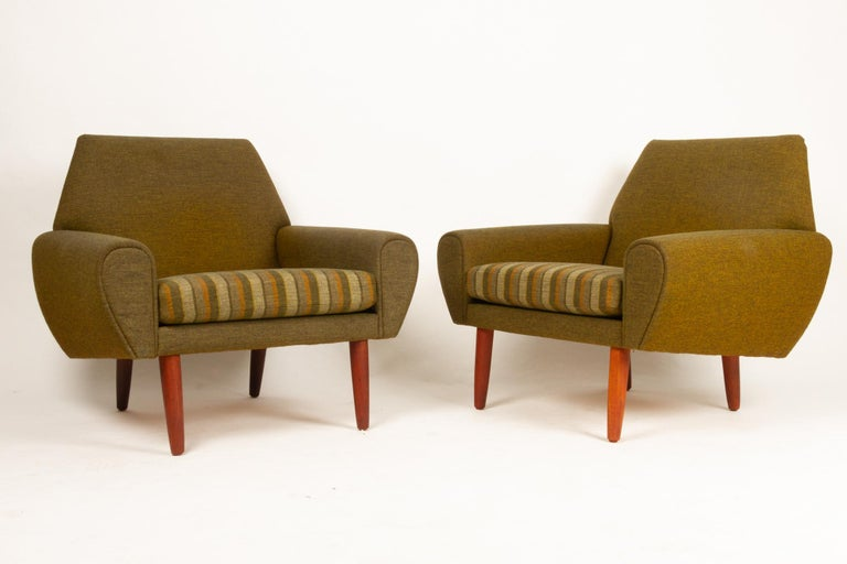 Danish pair of lounge chairs by Kurt Østervig, 1960s. Mid-Century Modern pair of green upholstered easy chairs with spring cushions. Attributed to Danish designer Kurt Østervig. Standing on round tapered legs in solid teak. Very comfortable and
