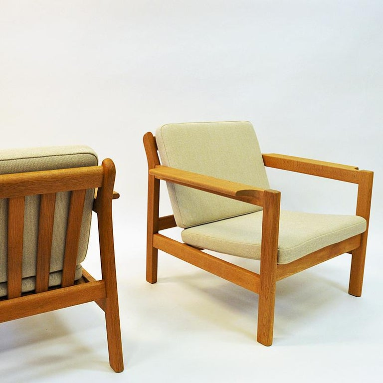 Lovely pair of Børge Mogensen armchairs model 227 for Fredericia Stolefabrik, 1960s, Denmark. The chairs are made of oak and have newly upholstered back and seat cushions in cream wool fabric dal 'Hallingdal' from GU Norway. Nicely tilted and soft