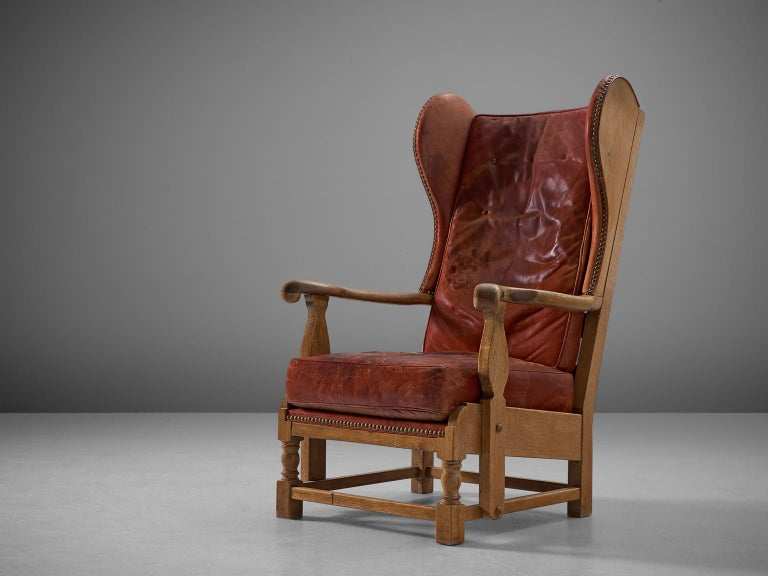 Lounge chair, red leather and oak, Denmark, 1930s.  This very rare early Danish lounge chair has the traits of a wingback chair whilst at the same time breathing the atmosphere of a gone century. This chair is easily pictured in a country house.