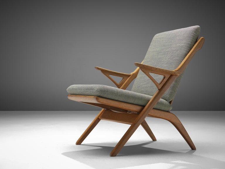 Armchair, in oak and fabric, Denmark 1960s.   Easy chair in solid oak with sculptural elements. What looks like a simple folding chair is in fact a wonderful armchair. The frame of solid oak has beautiful elements, such as the slatted back and