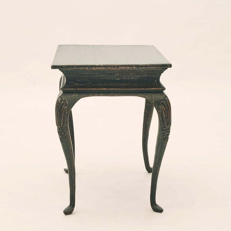 Rococo table black painted pine, good patina. Features a rectangular top with elegant apron. The table is raised on four cabriole legs with ornamented floral cuts at the top, Denmark, circa 1770. This Danish Rococo side table from the 1770s has a