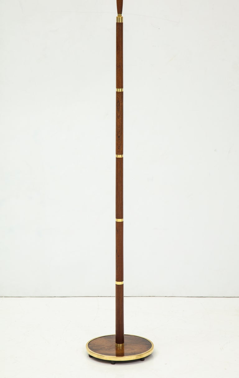 A Danish Fog & Mørup brass and brass floor lamp, circa 1960, a more unusual model with well figured rosewood and a rosewood base. Also with a rosewood handle to extend the lamp higher. Re-wired for the US. Good color.