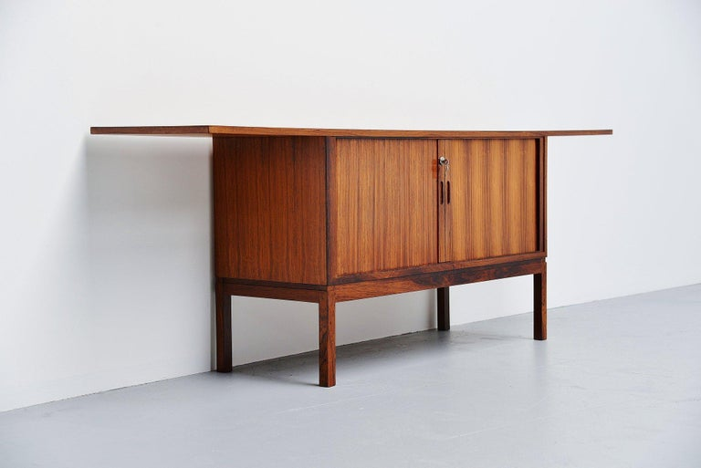 Very nicely and unusual shaped rosewood dry bar cabinet made by unknown designer or manufacturer, Denmark 1960. The dry bar has very nice tambour doors with storage space for bottles and glasses behind. The bar has a very nice rosewood grained