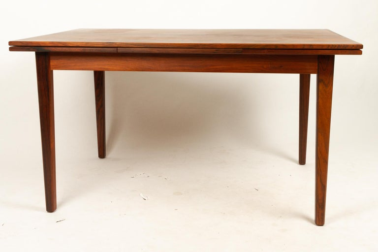 Danish rosewood extendable dining table, 1960s. Mid-Century Modern dining table with hidden extension leaves. Leaves pulls out from the ends of the table. Square tapered legs. Extended total length: 227.5cm. Original makers label on the