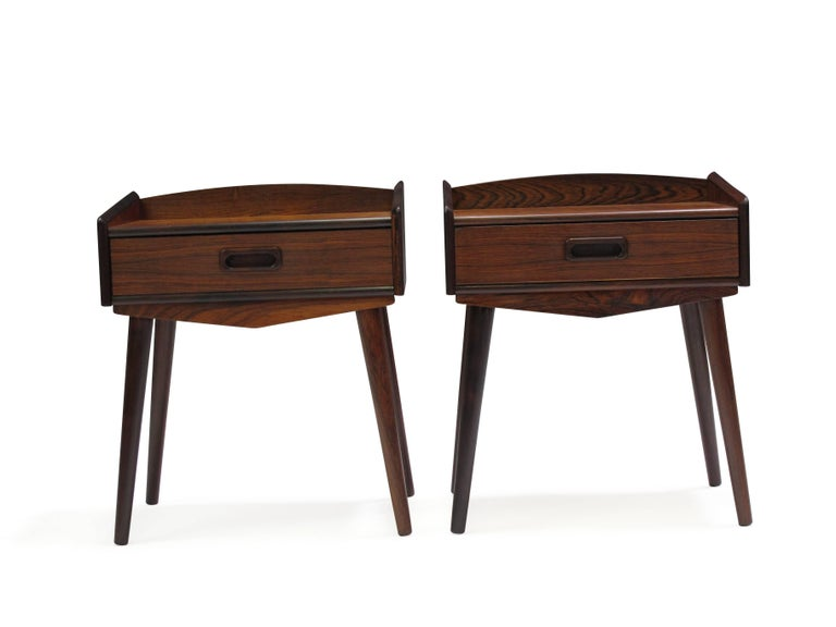 Midcentury rosewood nightstands each with one drawer with carved inset pulls, raised on splayed tapered legs of turned solid rosewood. Finely restored and in excellent condition.
