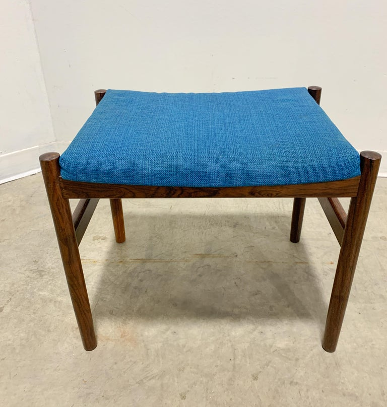 Beautiful Danish stool in Brazilian Rosewood made by Spottrup. Elegant frame of solid rosewood with striking blue original upholstery in good condition. Foam is still soft and comfortable as a footstool or vanity stool.   Measures: 21