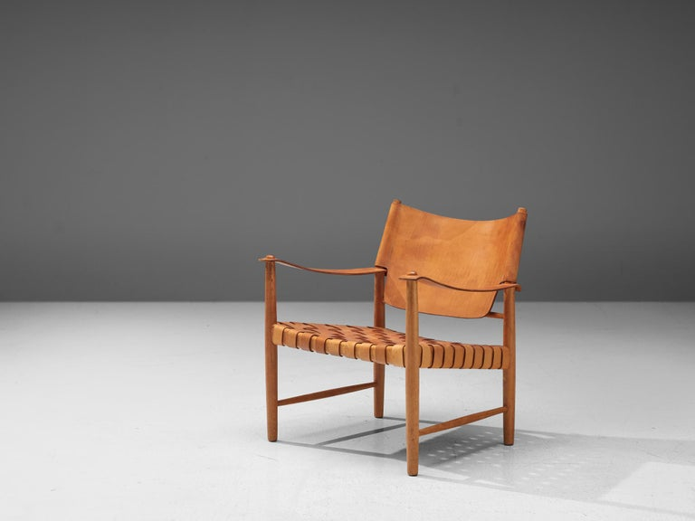 Safari chairs, patinated leather, beech, Denmark, 1950s  This elegant safari chair features wonderful patinated leather on both the seat and back. The patina on this chair create a vibrant look and the straps in the seat form a thick,