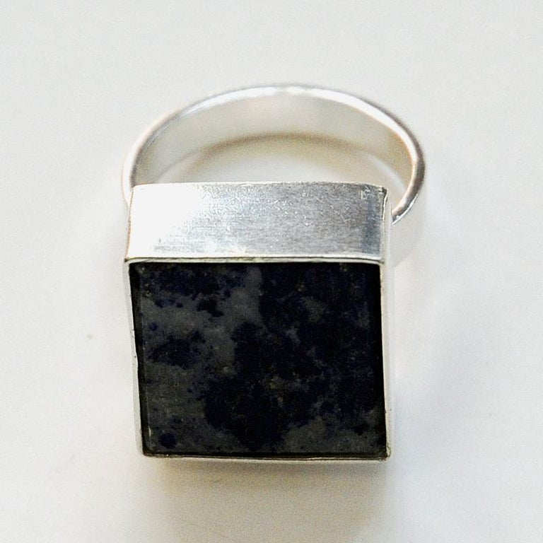 A square shaped silver ring with the Afghanistan Lapis Lazuli blue square stone on top embraced by a solid silver band edge holding the stone. Designed and made by Brødrene Bjerring (brothers Bjerring) in the 1970s Denmark. Signed Brdr Bje