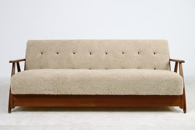 Beautiful authentic midcentury sofa. from the early 1950s made in Denmark, reupholstered, covered with great teddy fur fabric, like sheepskin, but softer to the touch, super cozy, tufted with brown leather buttons, the sofa has beechwood legs and