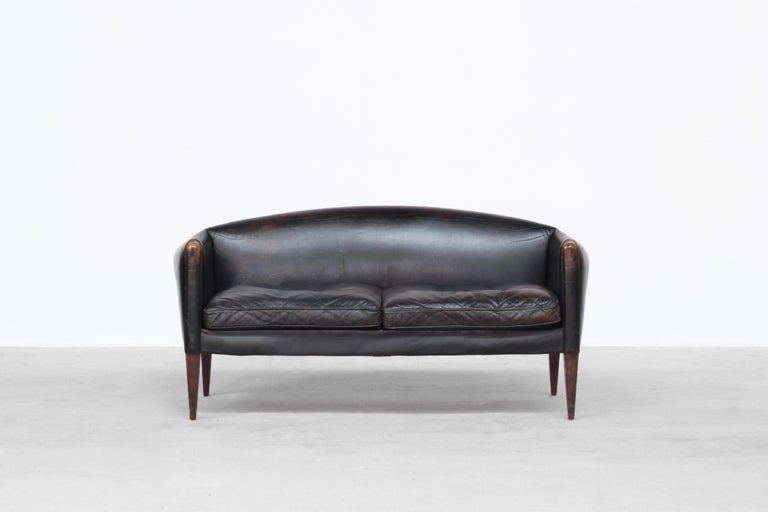 Very beautiful two-seat sofa designed by Illum Wikkelsø and produced by Holger Christiansen in the 1960s in Denmark. The sofa comes with a beautiful patinated black leather with traces of usage. It is ready for usage.