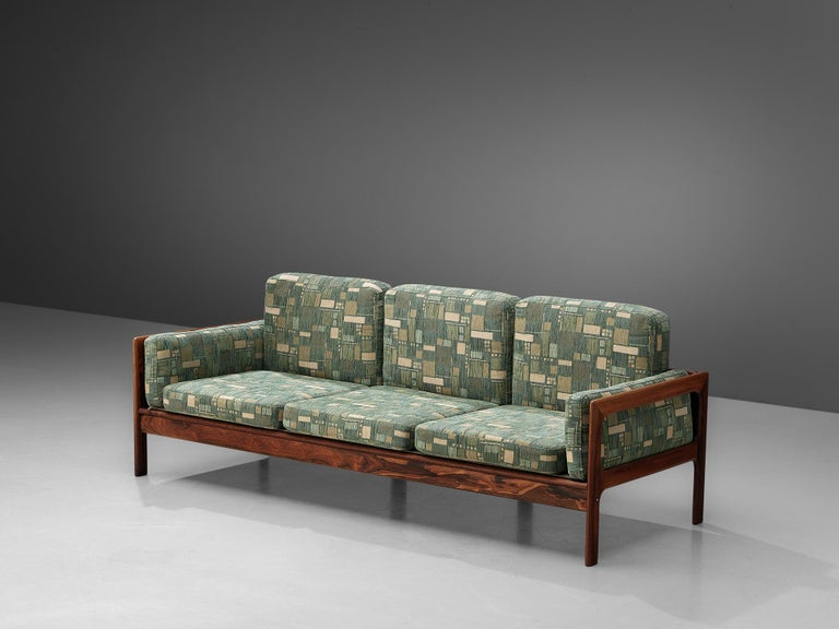 Three-seat sofa, green patterned upholstery, rosewood, Denmark, 1960s  This highly comfortable Danish three-seat sofa has a beautiful rosewood frame in an interesting geometrical and open shape. The frame is 'boxed' around the seating, showing