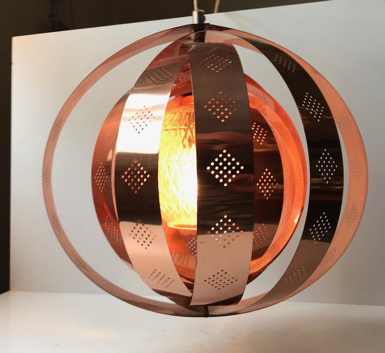 A rare Danish hanging light composed of rotating/modular copper rings and a centre shade in pressed glass. This Space Age design enables you to create a variety of different shapes. The most obvious ones being a moon or the outlines of the planet