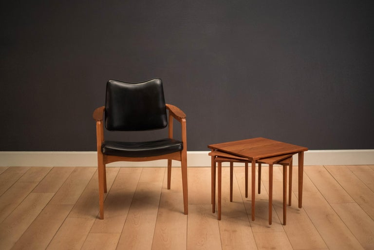 Early mid century set of stacking side tables manufactured by France & Daverkosen, Denmark. Table tops are constructed of solid planked teak with classic slender dowel legs. This set can be used as a coffee table or separate as three end tables.