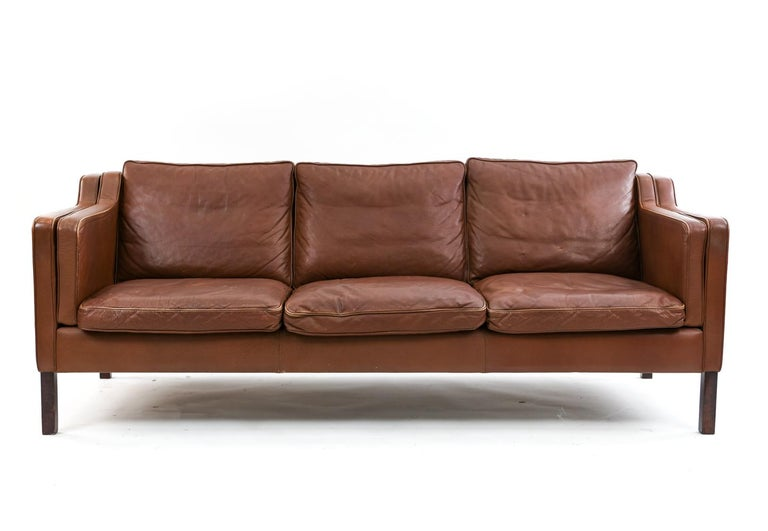 This Danish midcentury sofa was manufactured by Stouby. The design is in the manner of the iconic Borge Mogensen. This sofa is upholstered in attractively patinated brick colored leather and seats three comfortably.