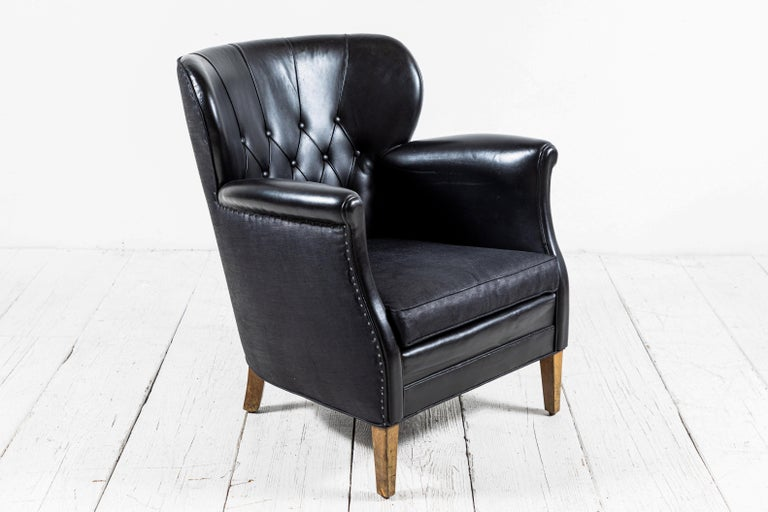 Danish style black leather tufted pair of chairs with slight winged sides. Black beetled linen and been added to the back of the chairs and seat cushions.