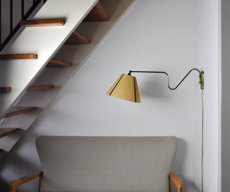 Brass wall lamp with two-piece swing arm and adjustable head. Swivel and wall mount made in brass, mounted with original shade in mustard color and four brown stripes.  Probably made by Lyfa, imprinted on the plug.  Measures: Arm length incl.