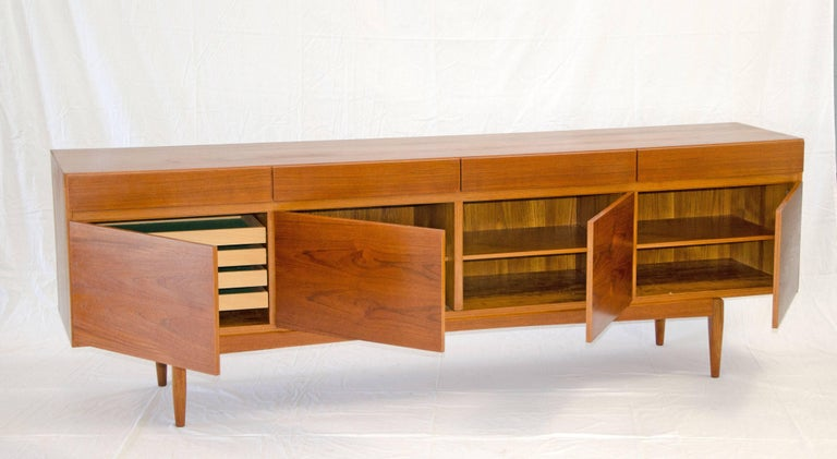 Extra long Danish teak credenza designed by Ib Kofod-Larsen with four storage drawers above four storage compartments. Three compartments have adjustable shelves and the fourth has four shallow pull out drawers for silverware or other uses. The four