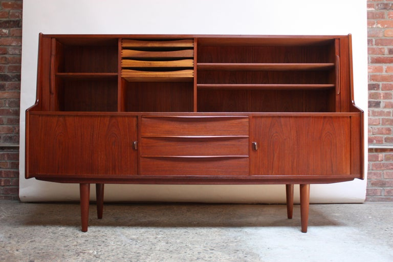 IB Kofod-Larsen highboard designed for Faarup. Early example (1950s) in dark teak with multiple storage compartments. Narrow profile and relatively diminutive size for its design / storage capability. Top two tambour doors open to reveal two