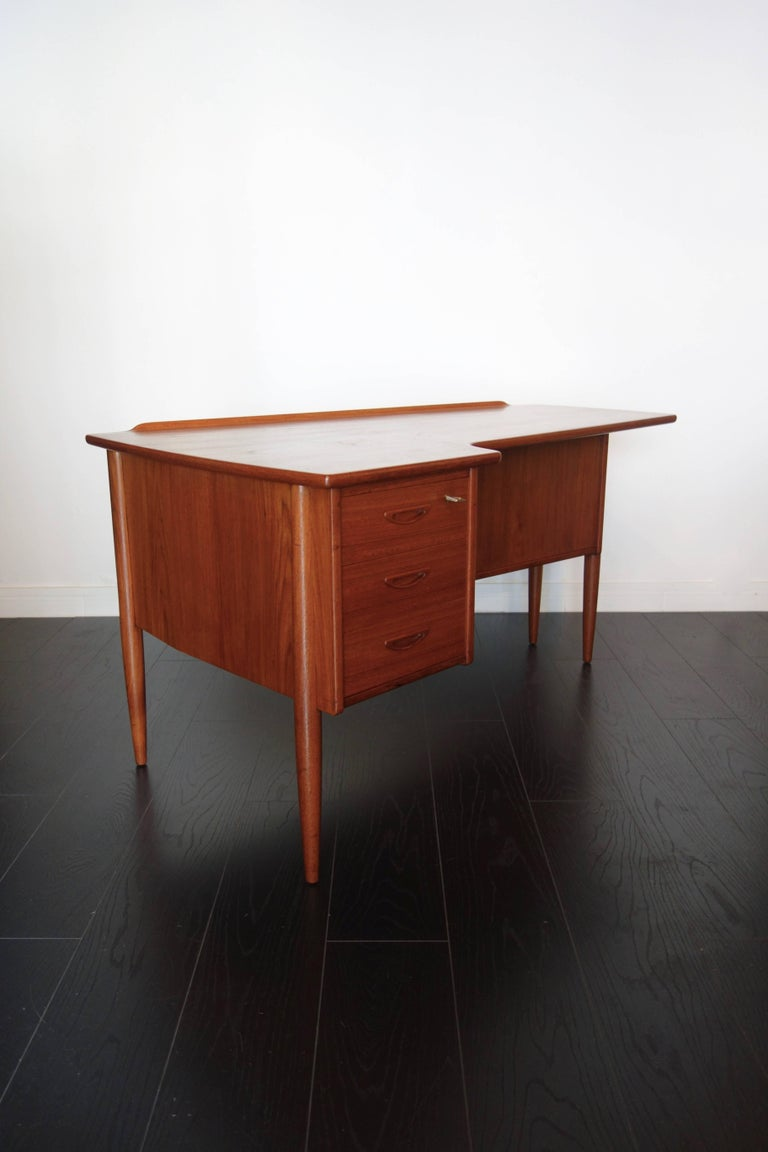 Double teak desk by Peter Løvig Nielsen. Made in the 1960s Danish. Boomerang shape, tapered round legs, three drawers with inlaid handles, recess and cupboard at the back with removable shelf. Keys and locks of origin. In exceptional condition: