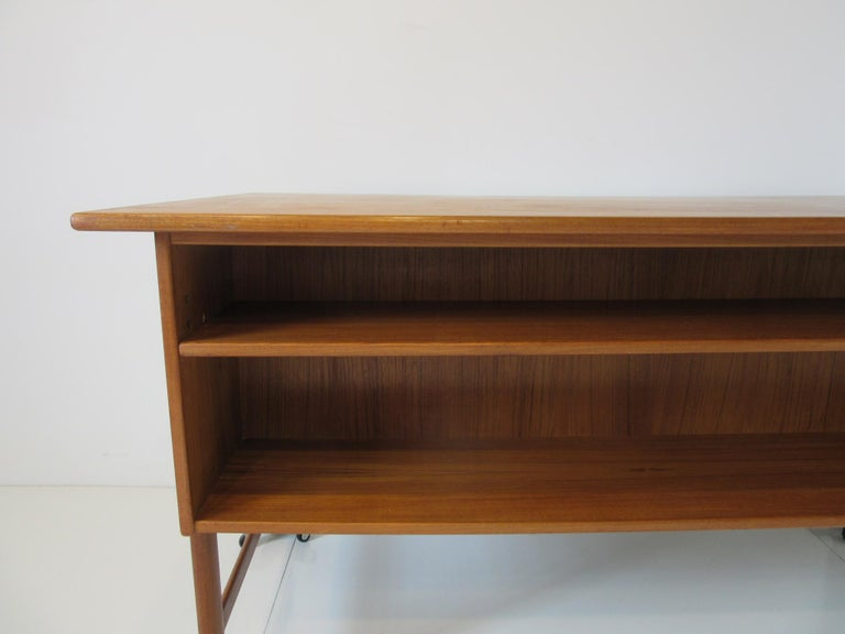 A well crafted teak wood desk with a built in bookcase to the backside having a adjustable shelve, to the front there's three drawers with a upper pullout writing surface, the other side has a file drawer all with teak handles. Designed in the