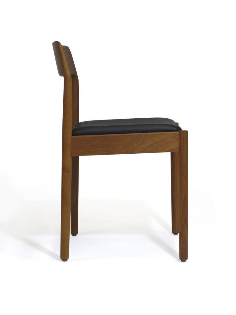 Four midcentury Danish dining chairs crafted of solid teak with newly upholstered seats in black vinyl.