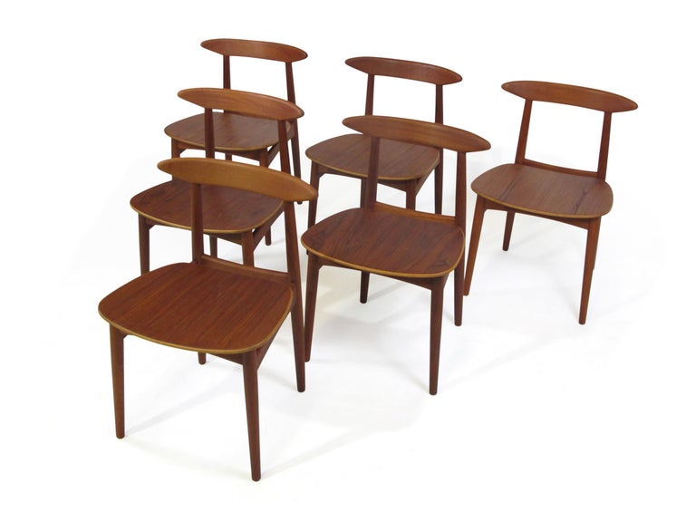 Six midcentury teak dining chairs attributed to Danish designer Kurt Ostervig. Solid teak frames, sculpted backrest with wood seats. The chairs have been professionally restored by our team of craftsmen. Excellent condition.