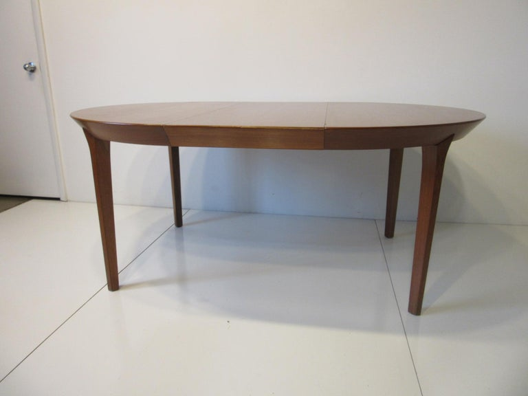 A well constructed teak dining table with 2 large 19