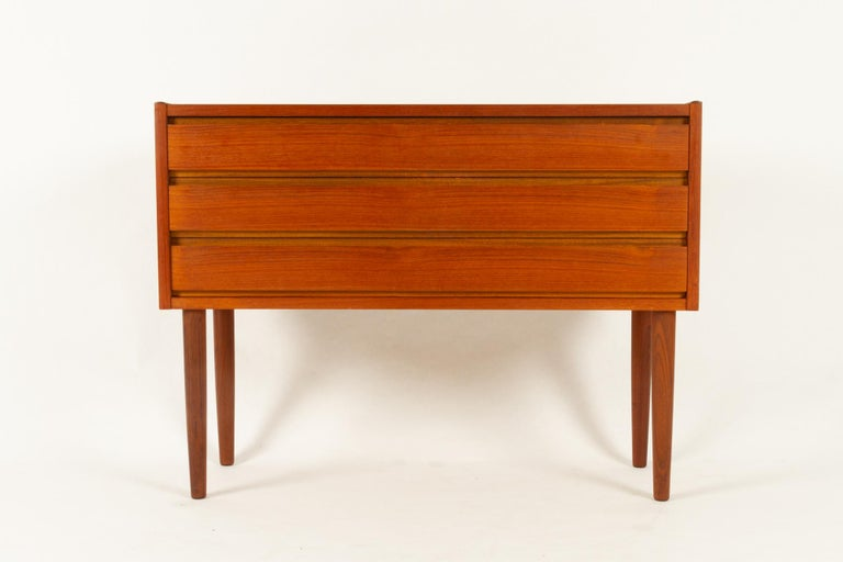 Danish teak dresser, 1960s Small and elegant teak dresser with three wide drawers and round tapered legs. Recessed handles. Original price sticker still on the back. Very good vintage condition. Gently cleaned, oiled and polished. Ready for use.