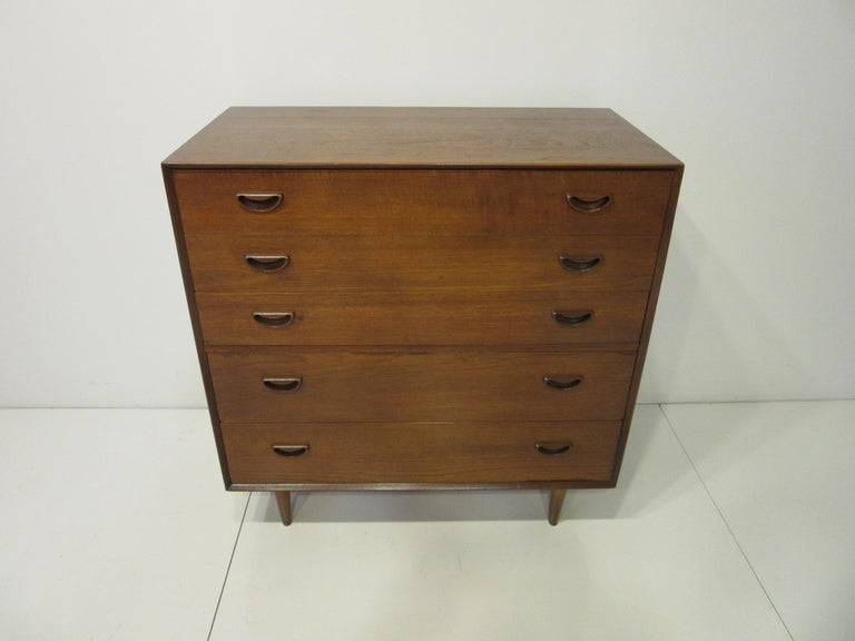 A five-drawer dresser / chest in teak wood with sculptural cut-out pulls with the top edges having dove tail finger joint construction. The two upper drawers have built in dividers and the lower drawers have plenty of storage. Retains the
