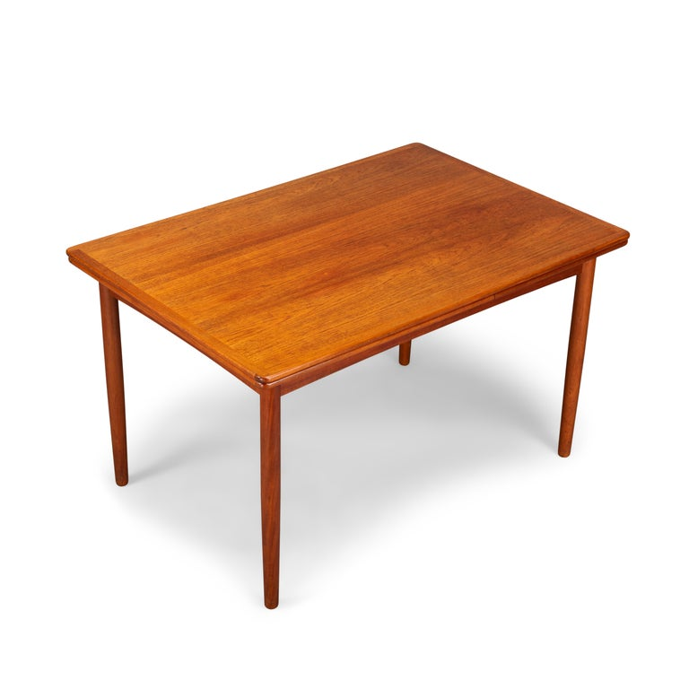 This Danish dining table was made in the 1960s. It features solid teak legs and two extension leafs which each measures 52 cm and extends the table to 2.30 cm. The extension leafs are hidden underneath the top. The color still matches really well
