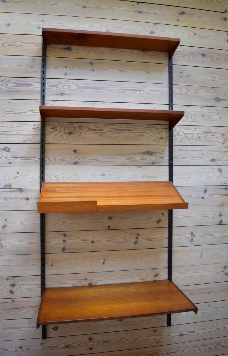 Set of four teak shelves by Kai Kristiansen and manufactured by FM Møbler, Denmark from the 1960s. This system comprises of two 24cm height adjustable shelves, magazine shelf, desk shelf and two hanging rails. Labelled by manufacturer.