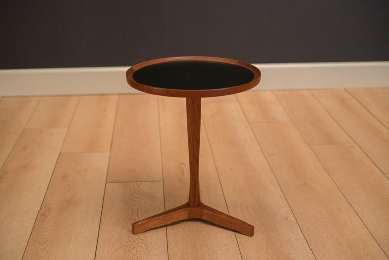 Mid-Century Modern side table designed by Hans C. Andersen for Artex. This piece has a black laminate inlaid top and a solid teak pedestal base.