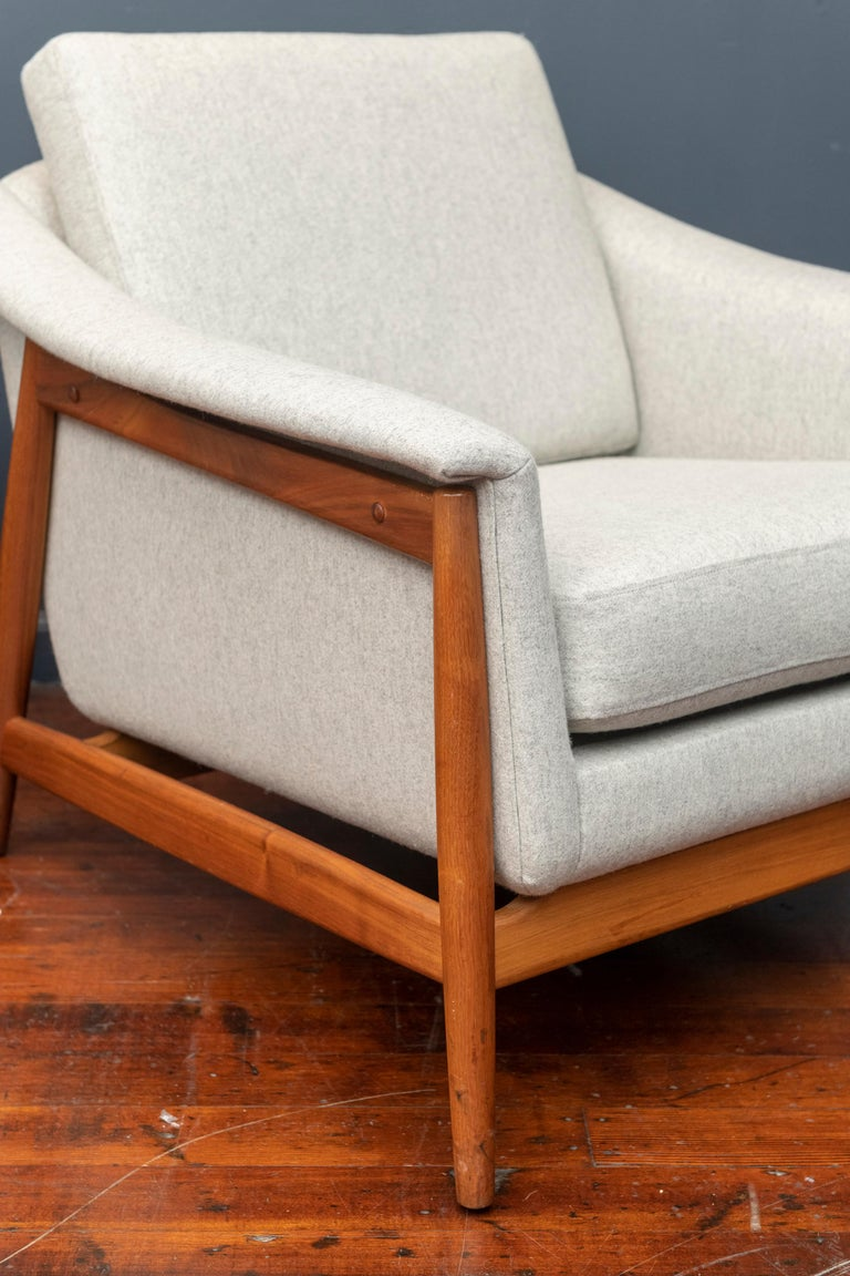Large comfortable Danish lounge chairs designed by Folks Ohlsson for DUX, Denmark. Newly upholstered in a light grey wool, framed in walnut, labeled.