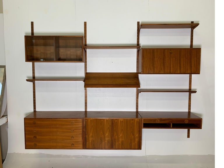 A beautiful and functional teak wall unit, produced by HG Furniture (Hansen and Guldborg) and designed by Rud Thygesen and Johnny Sorensen, Denmark, 1960s. With four wall-mounted uprights (steel with teak veneer), four large cabinets (one with four