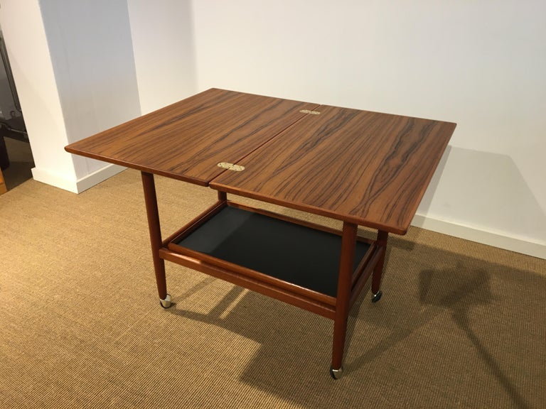 Grethe Jalk roll /serving/tray table from 1960 'with folding and swivel plate in teak with brass fittings. Sub shelf with removable tray teak edges and plate in black Linoleum. Dimensions: Unfolded 88 x 70, H 63 cm Folded D: 44 x 70 cm.