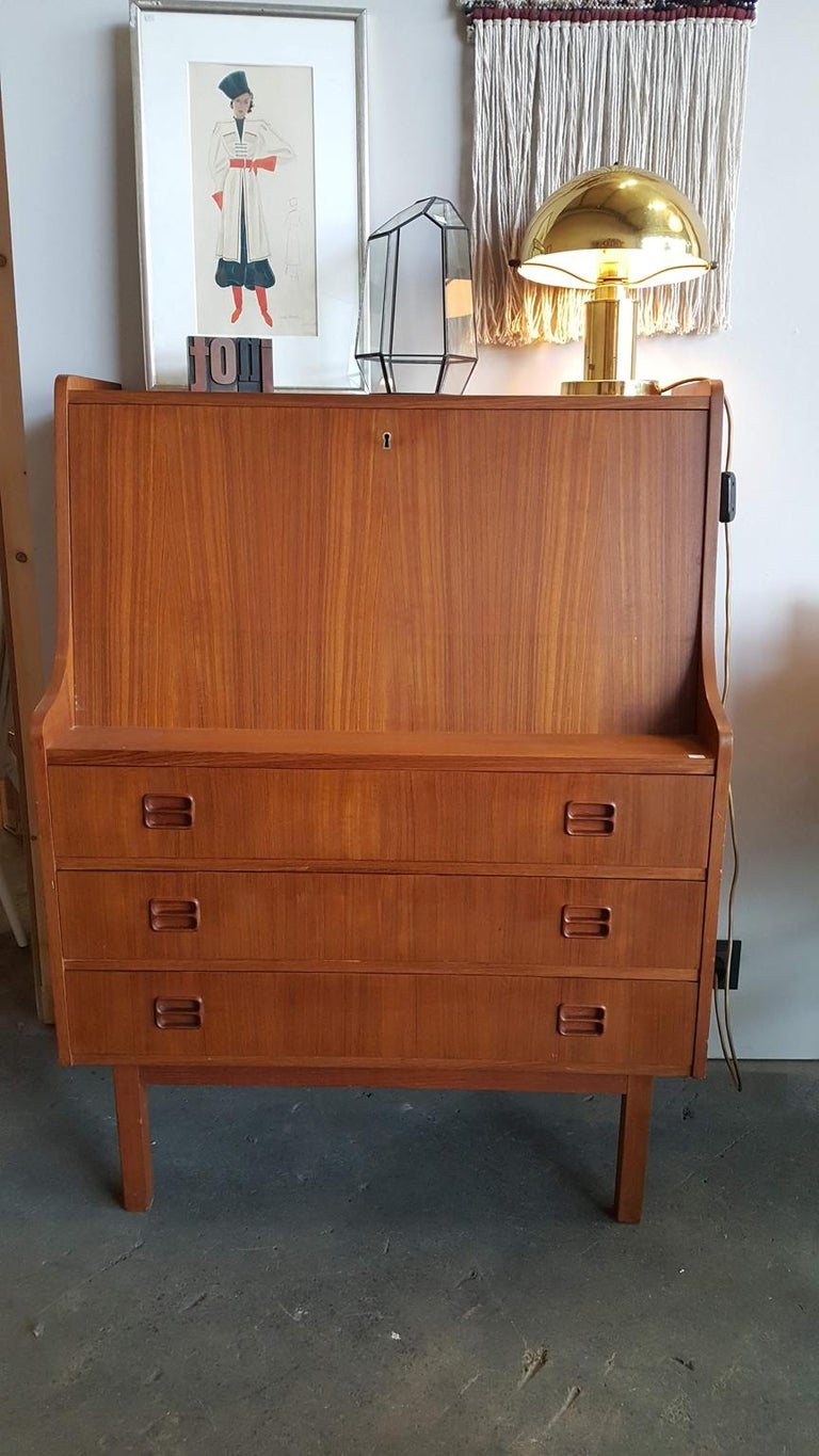 Nice little secretary from Denmark. Square body with a flap and three skirts. Flap lockable, key missing. Behind the flap there are compartments and 2 slippers. The body of the secretary is made of wood with teak veneer, the small drawers hunter the